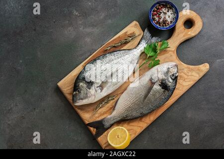 Flat lay fresh raw dorado fish on a wooden cutting board, dark rustic background. View from above - Stock Photo