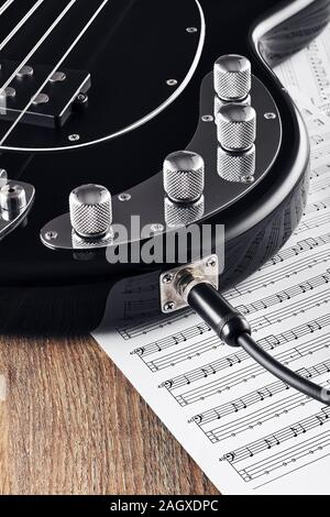 Black bass guitar and knobs with jack cable on sheet music and wooden table. Concept of music recording or composing. Close up view. - Stock Photo