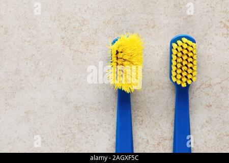 New and worn old toothbrush in contrast on marble background. Top view - Stock Photo
