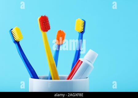 Multicolored toothbrushes and a toothpaste tube in a holder cup against blue background. Close up view. Dental care - Stock Photo