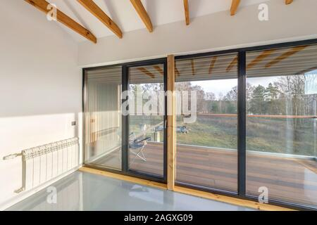 white empty apartment interior with panoramic windows and wooden rafter ceiling in vacation homestead house, Overlooking the nature in forest - Stock Photo
