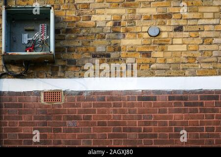 Bricks wall, with electricity / fuse box on it, opened, cover missing, cables visible. - Stock Photo