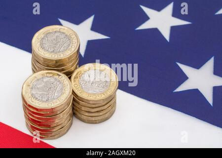 Stacked £1 coins on American Stars & Stripes flag. Metaphor US-UK trade deal post Brexit, Sterling exchange rate, Dollar value of Pound, UK exports US - Stock Photo