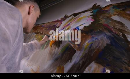 Artist designer draws an eagle on the wall. Craftsman decorator paints picture with acrylic oil color. Painter painter dressed in paint coat. Indoor. - Stock Photo