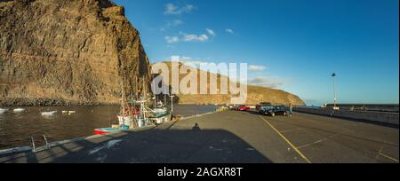 Wide panorama of Playa De Vueltas beach and Port with yacht and fishing boats at the atlantic ocean in La Gomera. A popular vacation spot for tourists - Stock Photo