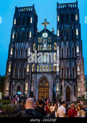 People at St Joseph's Cathedral lit up at dusk, Church Street, Hoan Kiem District, Hanoi, Vietnam, Southeast Asia - Stock Photo