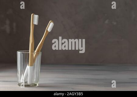 Two eco friendly bamboo tooth brushes in a glass. Zero Waste concept. Copy space for text - Stock Photo