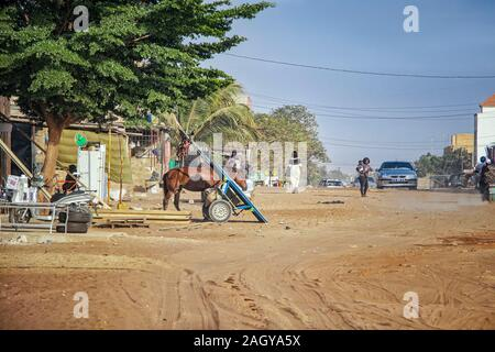 Mbour, SENEGAL - APR 26, 2019: Unidentified Senegalese woman with baby are walking down a dusty road in the middle of the city. There's a car on the - Stock Photo