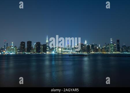 Long time exposure of New York City Manhattan midtown skyline at night viewed from Transmitter Park - Stock Photo