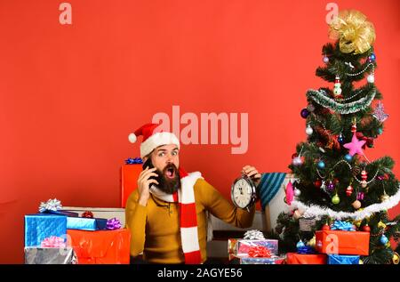 Santa Claus talks on mobile phone near fir tree on red background. Man with beard and shocked face sends greetings on New Year. Santa holds cellphone and clock. Winter holiday and technologies concept - Stock Photo