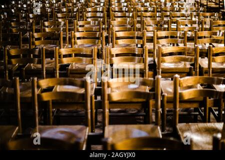 Front view of multiple church seats in a row perspective view inside Notre-Dame de Strasbourg cathedral