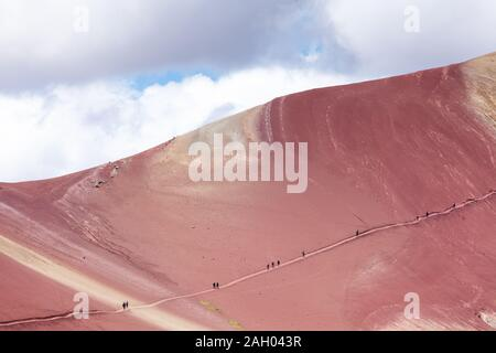 People climb to the top along a trail in the Rainbow Mountains of Peru. Peruvian Andes. - Stock Photo