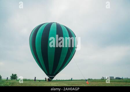 Inflating, unpack and flying up hot air balloon watermelon. Burner directing flame into envelope. Take off aircraft fly in morning blue sky. - Stock Photo
