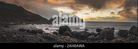 Panoramic view of the pathways and the bay at the coast called Giant's Causeway, a landmark in Northern Ireland, with the cliffs that surround the