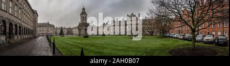 DUBLIN, IRELAND, DECEMBER 21, 2018: Panoramic view of Trinity College and its interior park, full of green grass surrounded by cobbled stone streets - Stock Photo
