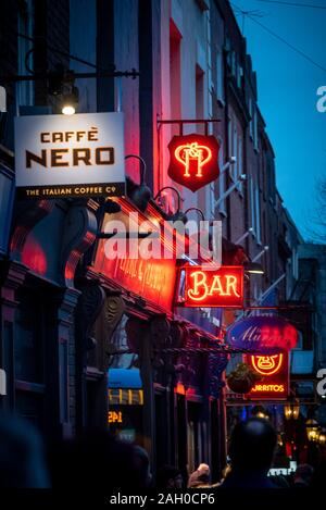 DUBLIN, IRELAND, DECEMBER 24, 2018: Glowing red neon lights, street signs and advertisements of cafes, bars and restaurants illuminating people walk - Stock Photo