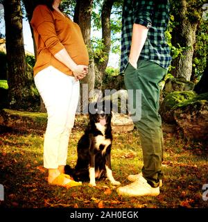 Dog sitting between the legs of a pregnant young woman and her husband - Stock Photo