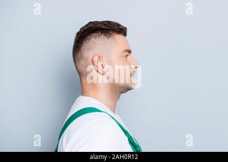Profile photo of handsome strong guy worker skilled engineer listen customer order not smiling reliable person wear green dungarees isolated grey - Stock Photo