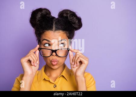 Photo of amazing dark skin lady sending air kisses touching eyeglasses looking wondered empty space listen rumours wear yellow shirt isolated purple - Stock Photo