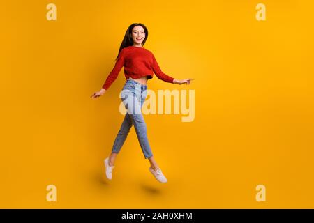 Full length body size photo of cheerful cute nice charming fascinating girlfriend running for sales jumping up wearing sneakes isolated over yellow