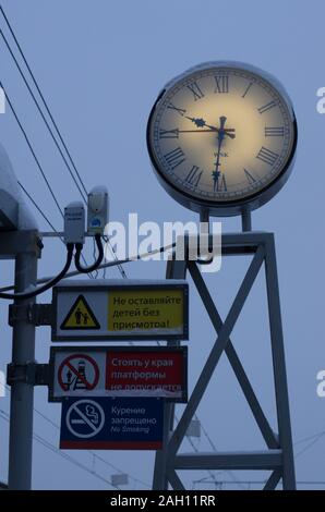 Vitebsky railway station,Saint Petersburg,Russia - January 24, 2019: Luminous clock with Roman numerals and information signs in Russian in the mornin - Stock Photo