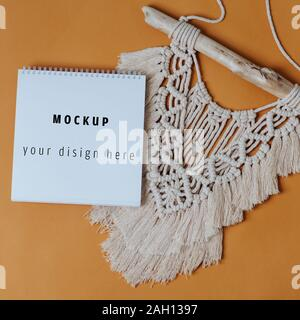 Mokeup spiral notebook on macrame tapestry close up over orange background - Stock Photo