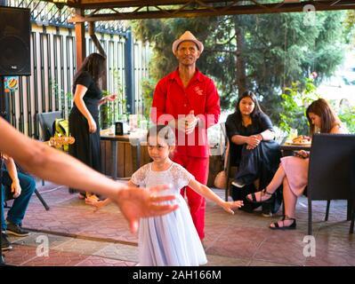 Bishkek, Kyrgyzstan - June 30, 2017: Little girl in white dress dancing. Man in red costume dances. Mexican party - Stock Photo
