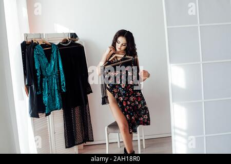 Beautiful brunette woman chooses things in the wardrobe - Stock Photo