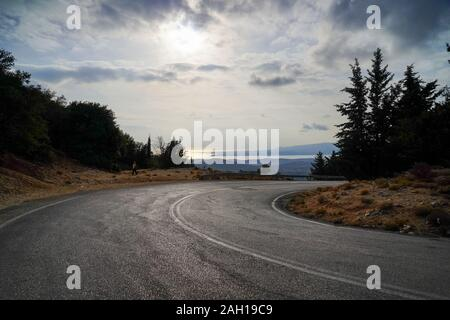 curving winding road through the pine forest of Zakynthos Island, Greece - Stock Photo
