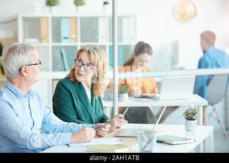 Mature businesswoman in eyeglasses talking to the mature businessman while they sitting at desk with laptop at office