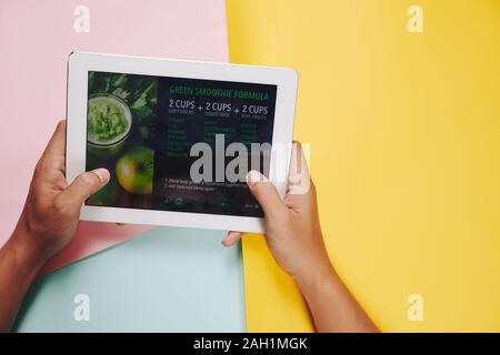 Hands of man holding tablet computer with green smoothie recipe on the screen Stock Photo