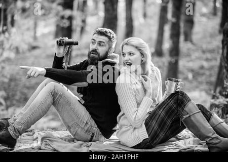 wild outdoor. couple in love relax in autumn forest with tea or coffee. camping and hiking. surprised girl drink mulled wine. bearded man shocked watch with binoculars. Spring mood. Family picnic.