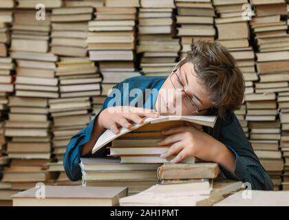 Sleeping boy as a pupil in the library with a big stack of books. Close up portrait. Knowledge concept - Stock Photo