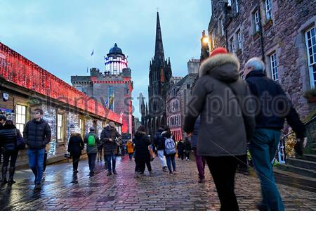 Edinburgh, Scotland, UK. 23rd  Dec 2019. Christmas lights and busy with tourists in the Royal Mile as dusk approaches. View of Camera Obscura. Credit: Craig Brown/Alamy Live News - Stock Photo