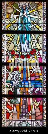 Stained-glass window depicting Our Lady of Lourdes appearing to Bernadette Soubirous in the cave of Massabielle. The Sanctuary of Our Lady of Tylicz. - Stock Photo