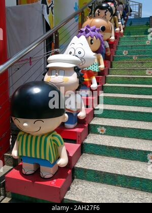 Seven cartoon characters lined up a set of stairs adjacent to Kowloon Park. - Stock Photo