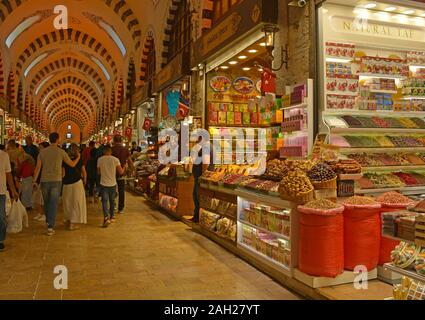 Istanbul, Turkey - September 19th 2019. Tourists walk past shops selling spices, teas and dried fruit in the historic Egyptian Spice Bazaar in Eminonu - Stock Photo