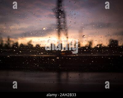 Blurred silhouette of industrial setting through car glass with raindrops against window. Sunset and clouds in background - Stock Photo