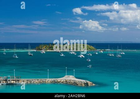 Sailboats at anchor by the Ilet Du Gosier Lighthouse as seen from suburban Pointe-a-Pitre on Guadeloupe.  The large flat island of Marie-Galante is on - Stock Photo