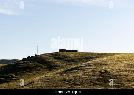 Minimalist natural scenery of hills covered with grass with constructions on top under clear blue sky in sunny day - Stock Photo