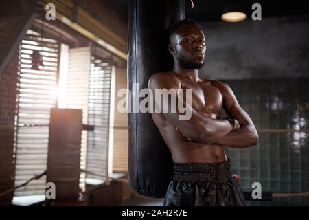 Portrait of African young shirtless man leaning on the punching bag and looking at camera in gym - Stock Photo