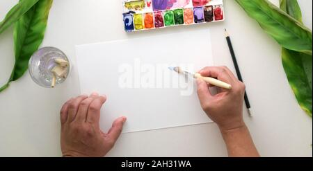 Top view of young professional artist painting on sketch paper with water colour in his workplace - Stock Photo
