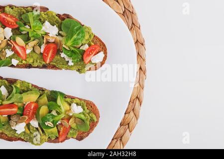 Two rye bread toasts with mashed avocado, tomatoes and feta cheese. Healthy appetizer on the white plate, top view - Stock Photo