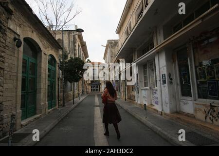 Woman crosses a street in the old section of the city of Limassol, Cyprus