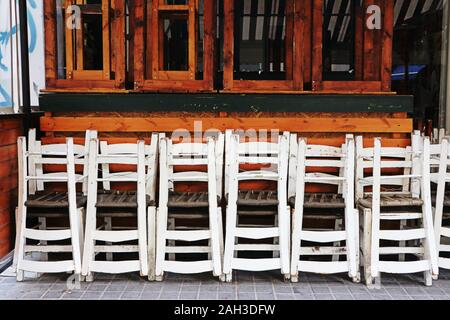 White traditional wooden chairs stacked outside restaurant with brown wood window frames - Stock Photo
