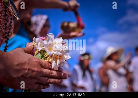 A spiritual girl holding a bouquet of wildflowers in her hands. Happy group of young friends having music on the beach. Young spiritual women sing - Stock Photo
