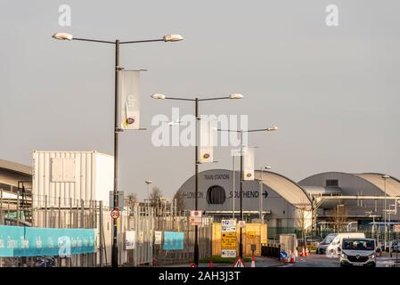 Construction underway during further expansion at London Southend Airport, Essex, UK. Train station and car park. Fencing and hoarding. Cones - Stock Photo