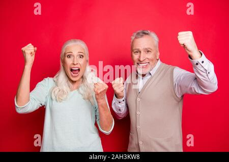 Close up photo beautiful she her he him his aged white hair guy lady partners hold hands arms fists raised yelling loud football goal wear sweater - Stock Photo