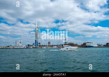 A power boat moves past the  Emirates Spinnaker Tower overlooking Portsmouth Harbour. The tower is 170m tall and has a viewing deck - Stock Photo