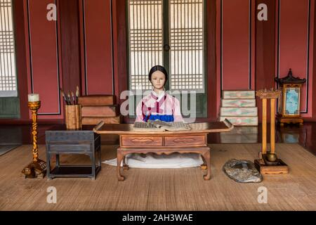 Dressed mannequin of a maid in an imperial palace reading books at Hwaseong Haenggung Palace, the ornate residential palace built for King Jeongjo whe - Stock Photo